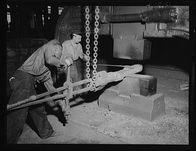 Giant tongs hold forging. Forging part of a large gun in an eastern Navy yard. This is one of eleven Navy arsenals which have stepped up production to top speed for the war program