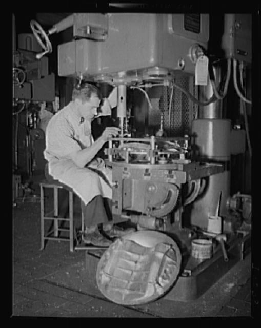 Skilled workers needed on torpedoes. Skilled drill press operator working on a torpedo bulkhead in an eastern Navy arsenal
