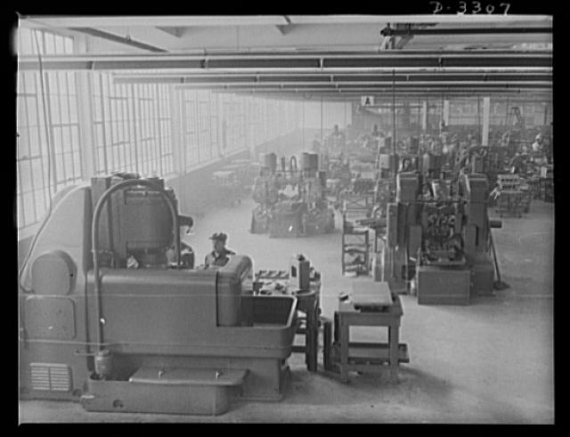 When an automobile plant changes over to war production much of the regular plant equipment is ready for use without changes. This big grinding machine, for example, is just as adaptable to shell output as to automobile manufacture. Oldsmobile, Lansing, Michigan