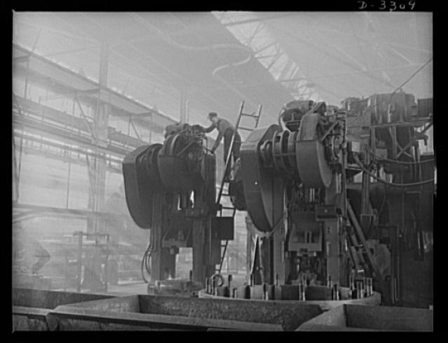A huge forge manner is taken off its regular peacetime duties in an automobile plant and put on war Production. When workmen have finished their conversion job, the big fellow began shaping crankshafts for defense. Oldsmobile, Lansing, Michigan