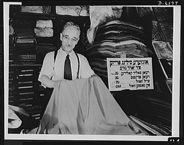 Posting ceiling prices in foreign languages. Mr. H. Brodskey is proud of the quality of the yard goods he carries at his marketplace stand in New York's East Side. He is proud too that he is aiding his government in the fight against inflation by displaying a price ceiling sign printed in Yiddish so that it may be easily understood by his customers