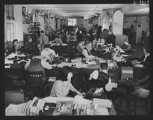 Office of War Information News Bureau. The News Bureau room of the OWI. It is arranged much the same way as the city room of a daily newspaper. Here, war news of the world is disseminated. In the foreground, are editors' desks handling such special services as trade press, women's activities, and campaigns. The news desk is in the background