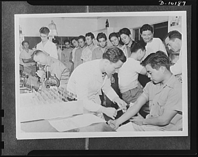 Japanese-American volunteers. Impatient to go through the last step in their physical examination--the blood test, these AJA [Americans of Japanese ancestry] volunteers on Kauai press forward to have samples of their blood taken by Sergeant Bernard G. Borden of Hartford, Connecticut (left) and Sergeant Romeo L. Giguere of Detroit, Michigan (right). In the background, standing is Corporal Henry Crowder of Detroit, Michigan and sitting is Captain John F. Little, Jr. of Horfold, Virginia. Volunteers who passed their physicals were sent to a provisional camp pending trans-shipment to Oahu. They were administered the oath of induction on Kauai, however