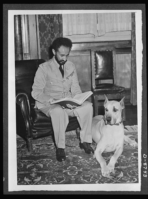 American military delegation calling on Haile Selassie. With his pet dog, Bull, alertly resting at his side, His Majesty, Haile Sellassie, Emperor of Ethiopia, was caught in this picture while reading an official report. These pictures are the first to be taken for publication since His Majesty's return to become a fighting member of the United Nations