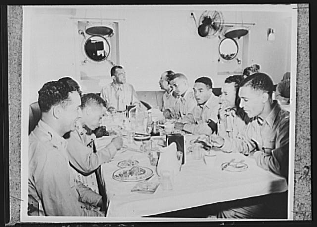 U.S. Negro troops on way to Liberia. Aboard a U.S. Army transport bound for Liberia, Africa officers of the Negro troops sit down for a meal. Left to right around the table; Lieutenant Abner R. Branch, oral surgeon; Captain Harsba F. Buoyer, war vetern and distinguished doctor; Captain W.D. Nabors; Warrant Officer Brice; Lieutenant Henderson, pathologist and tropical medicine expert; Edgar Rouezeau, correspondent of the Pittsburg Courier; Lieutenant Ned Manley, orthopedic surgeon and professor at Howard University , famous Negro institution, before entering the service; and Lieutenant Goldsberry, physician and holder of a master's degree in public health from Harvard University