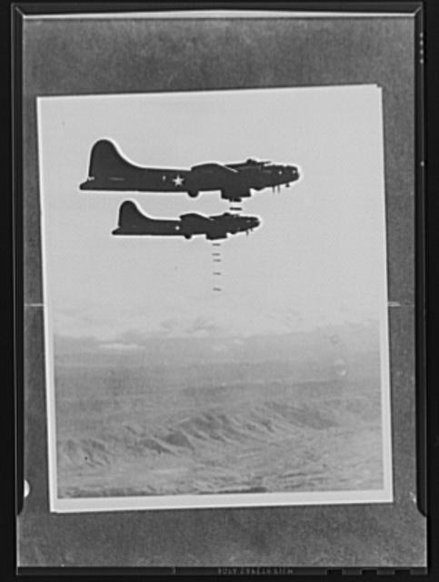 Bombs away! At the proper moment the bombardiers release their load. A salvo, such as this, finds all bombs dropping in a straight line, because each of them continues, for a time, at the same forward speed it had acquired while in the plane's bomb bay. Three miles down below is the target, the objective of this raid. After this salvo, the bombardier may direct the pilot to fly back over the target for another crack at it