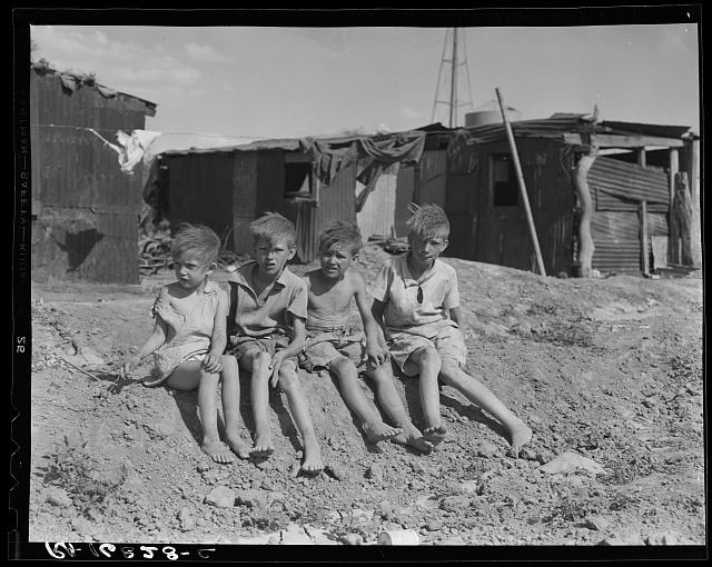 Children of migrant cotton field workers from Sweetwater, Oklahoma. Eight children in the family. Note the housing. Near Casa Grande project, Arizona