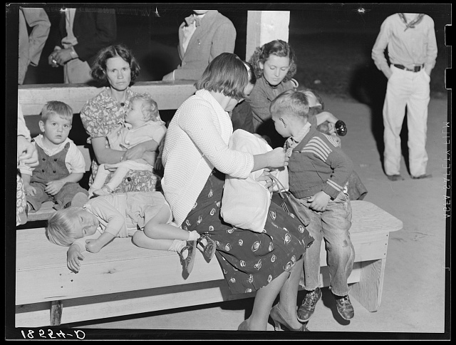 Tired mothers and tired children at the end of the Halloween party at Shafter migrant camp, California
