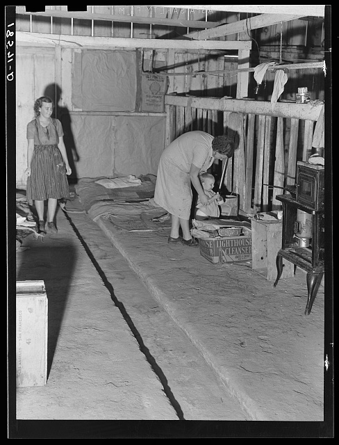 Living conditions of workers in agriculture on whom depend the crops of California. Family of migratory cotton pickers, originally from Oklahoma, living in abandoned cow barn. Note bed in corner. Kern County, California
