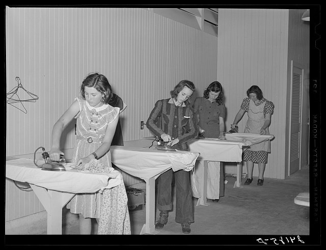 Ironing clothes in utility building. Tulare migrant camp. Visalia, California