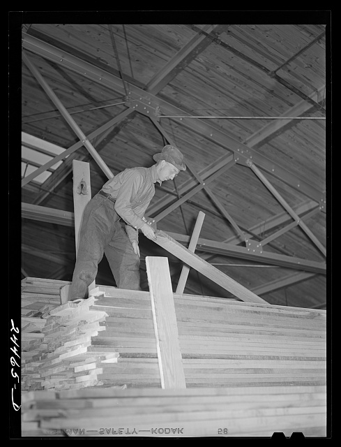 Worker unloading lumber from stacks. Dimension lumber plant. Dailey, West Virginia