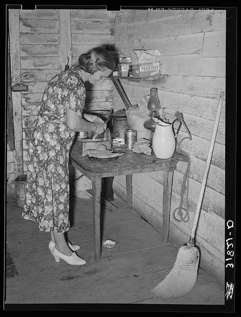 Mrs. Adams, wife of farmer near Morganza, Louisiana, preparing sweet potatoes for dinner. Family will shortly be helped by FSA (Farm Security Administration)