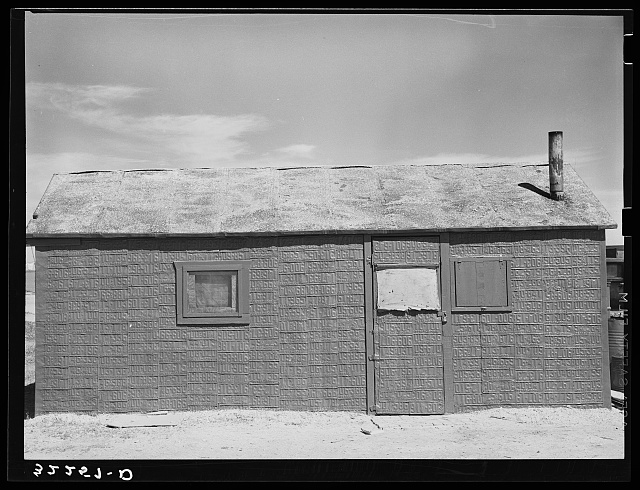 House in shantytown on Nueces Bay, Corpus Christi, Texas. Notice siding of old automobile license plates. House is occupied by migrant workers