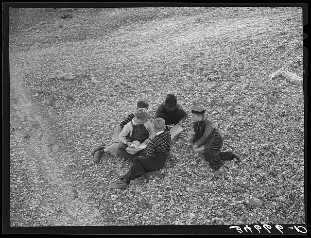 Children playing in the waste in the gin yard on their way home from school. West, Texas
