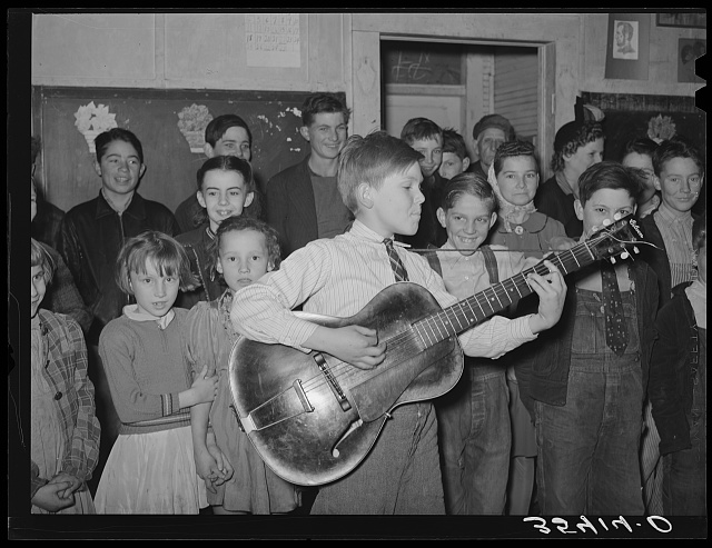 "Boy playing and singing ""Sipping cider through a straw"" at pie supper in Muskogee County, Oklahoma. See general caption 24"