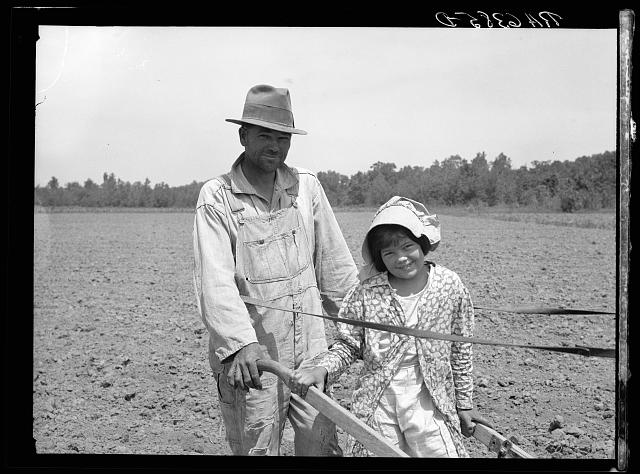 R.E. Sneed, rehabilitation client and eight year old daughter on cotton cultivator. Near Batesville, Arkansas