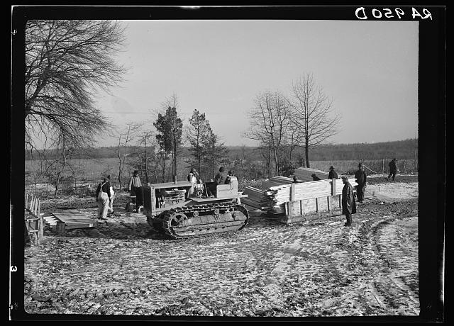 Wooden sleds drawn by tractor bringing supplies from main road to project at Berwyn, Maryland. During the winter months tractors and mud sleds furnish the only method of getting from the main road to the project. Transportation was chief problem at the new construction