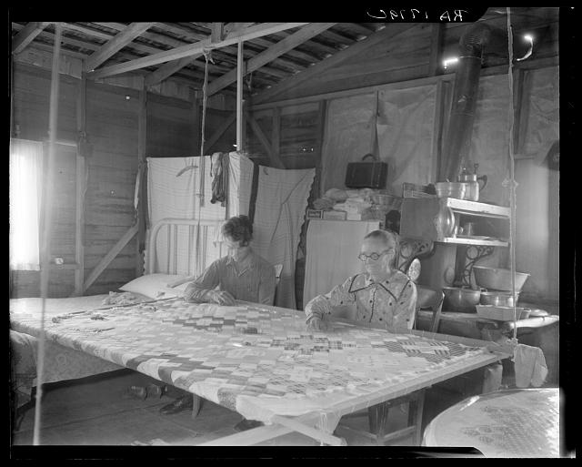Grandmother from Oklahoma with grandson, working on quilt. California, Kern County