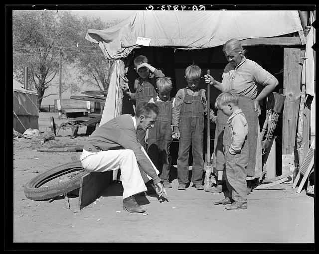 Tom Collins, manager of Kern migrant camp talking with drought refugee and her four sons. California