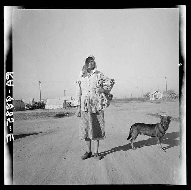Cotton picker on her way to the cotton field. Kern migrant camp, California