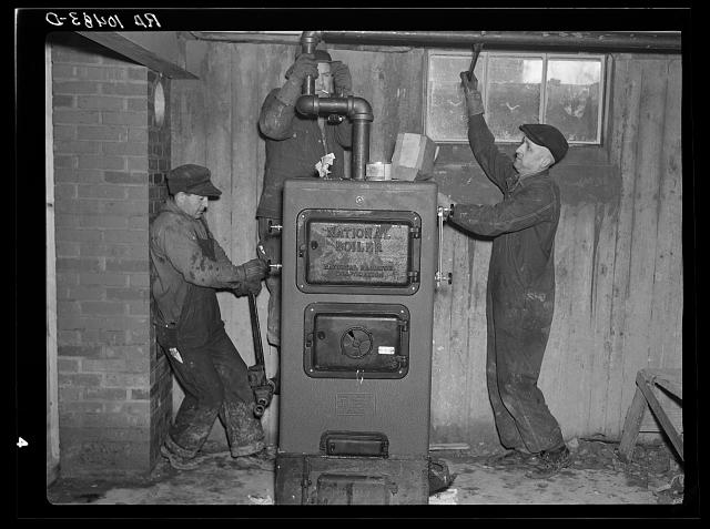 Plumbers at work in the basement of a house on the Greenhills project, Ohio
