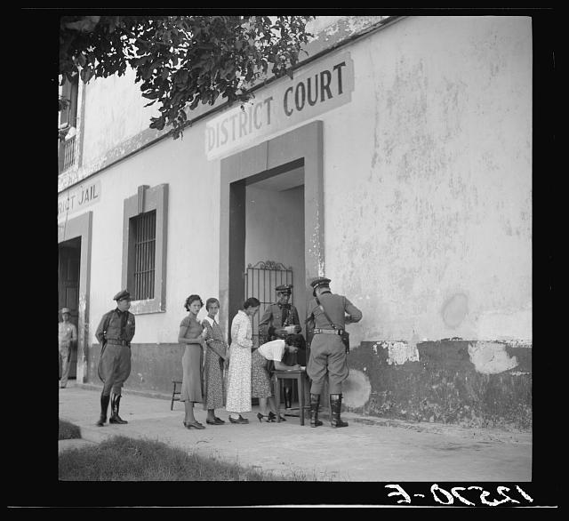 Examination and registration of witnesses and members of the audience at the trial of the Nationalists. Every person entering the courtroom was searched for arms. Ponce, Puerto Rico