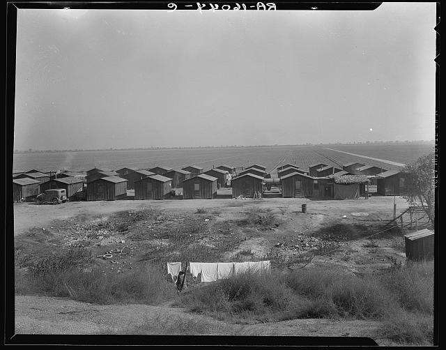 Company housing for Mexican cotton pickers, showing the San Joaquin Valley in the background. South of Corcoran, California