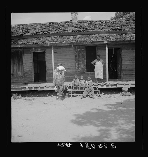 Negro wage laborer and part of his family. He is coming home from the commissary with a week's rations. Macon County, Georgia