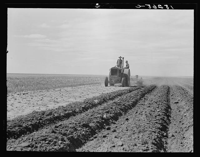 Dust bowl farmer driving tractor with young son near Cland, New Mexico