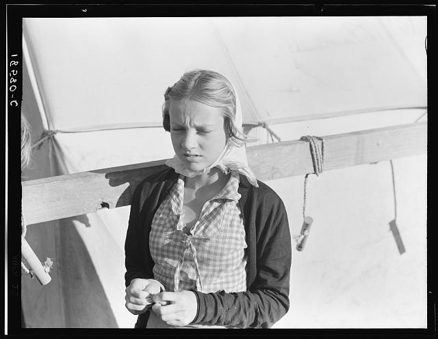 Young girl, migratory worker, beside the tent in which she lives. Kern County, California