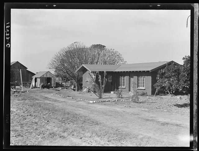 Rural rehabilitation, Tulare County, California. In 1936 this family was on relief. With a Farm Security Administration (FSA) loan of seven hundred and eighty dollars, they were able to purchase and install an irrigating pump for the vineyard, a team, and the balance gave them subsistence and operating expenses for the first grape season. This house which the family has just finished building is made of adobe bricks, made from clay on the farm. The cash cost in building the house was about six hundred dollars