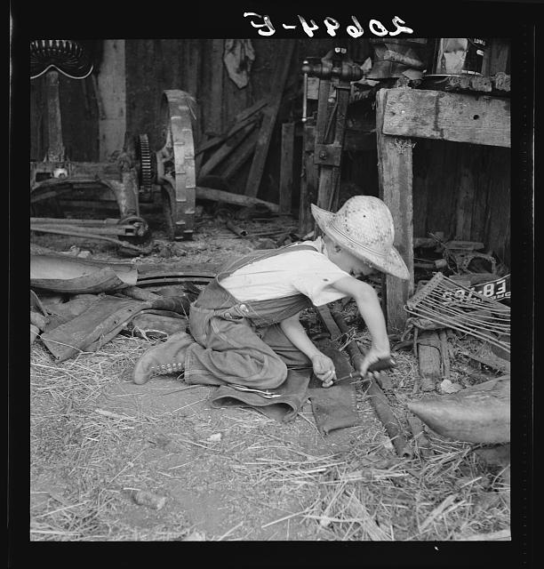 Young farm boy. Younger brother trying to make a holster from the leather of an old coat. Oregon, Jackson County, near Medford