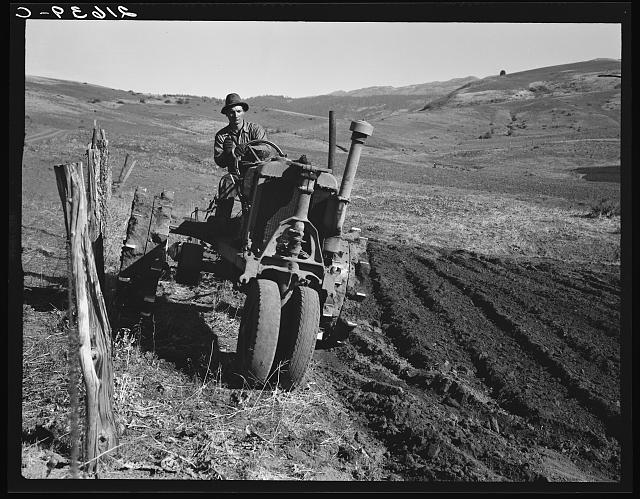 Young farmer plowing while other co-op members work in the sawmill. The tractor does work for five member families. Ola self-help sawmill co-op.  Gem County, Idaho