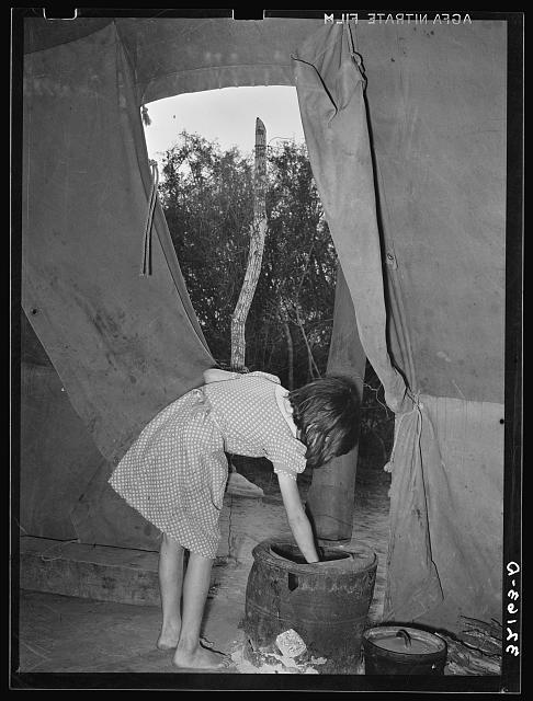 Child of white migrant worker building fire in heating stove in tent home. Harlingen, Texas