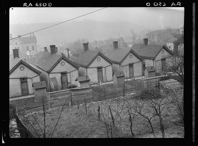 Row of identical houses off Eastern Avenue, in Cincinnati, Ohio, showing backyard outhouses. Ohio River Valley is in the distance