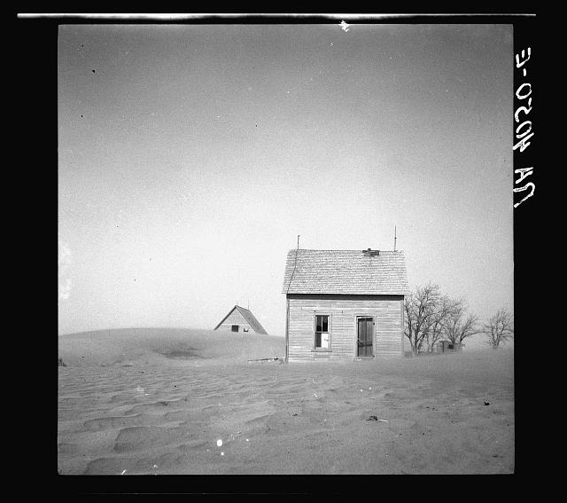 Sand whirling around house and barn. Cimarron County, Oklahoma
