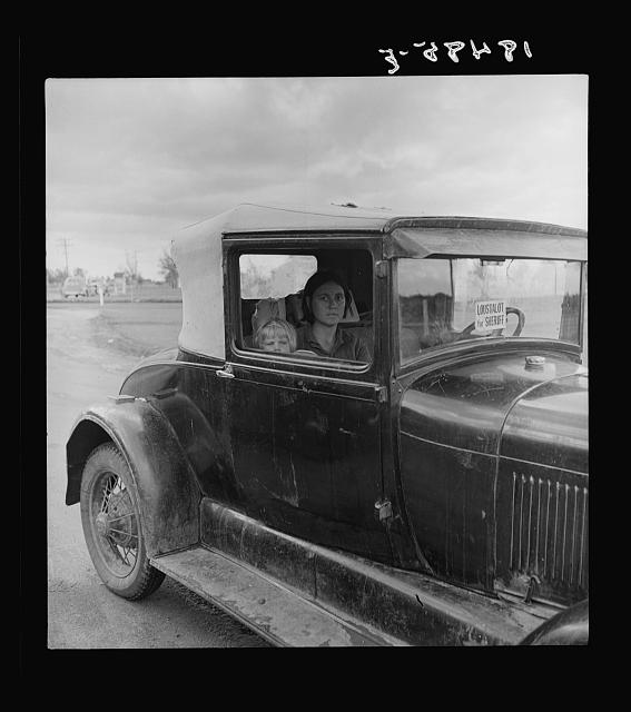 During the cotton strike, the father, a striking picker, has left his wife and child in the car while he applies to the Farm Security Administration for an emergency food grant. Shafter, California