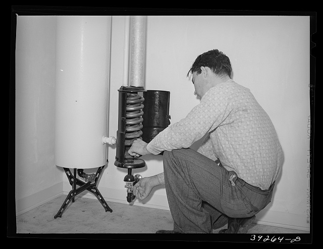 Lighting hot water heater in house at the Kearney Mesa defense housing project. This young man came out to California from Oklahoma ten years ago. He has been an agricultural worker and has lived in various FSA (Farm Security Administration) camps. He is now employed as a painter at the Consolidated Aircrafts