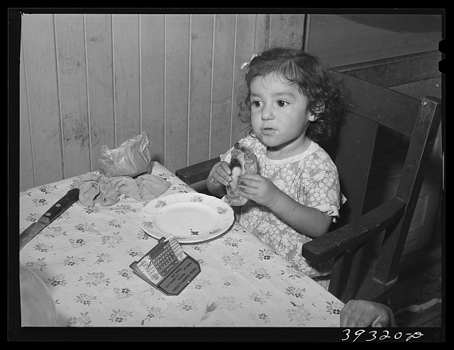Little Mexican girl eating enchilada for lunch. San Diego, California