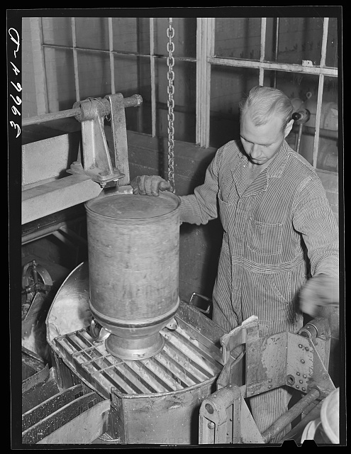 Dumping milk into container where it will be weighed and the weight automatically recorded at the Dairymen's Cooperative Creamery. Caldwell, Canyon, Idaho