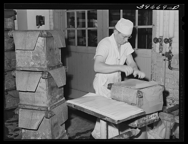 Putting layer of waxed paper over tub of butter at the Dairymen's Cooperative Creamery. Caldwell, Canyon County, Idaho