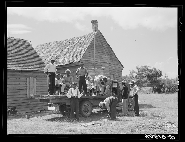 Part of a crew of thirty-five migrants who come up in this truck and who stay in the farmhouse in background. It is Sunday and they are going into town for the day