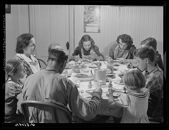Dinner hour at the home of Mr. J.H. Dube, French-Canadian potato farmer, after he and the boys had finished a day's work in their potato field in Wallagrass, Maine