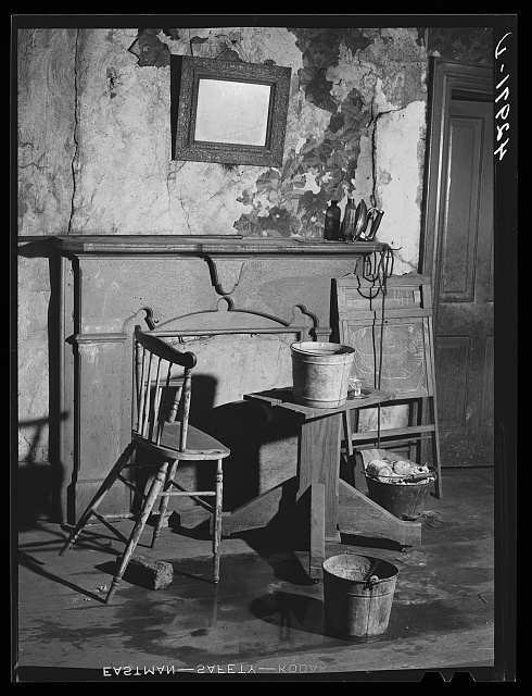 Buckets placed in room to catch water from leaky ceiling in a house in Mount Washington district. Beaver Falls, Pennsylvania