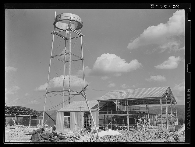 Construction, new community dimension woodworking factory for making furniture. Showing water tower. Tygart Valley, West Virginia