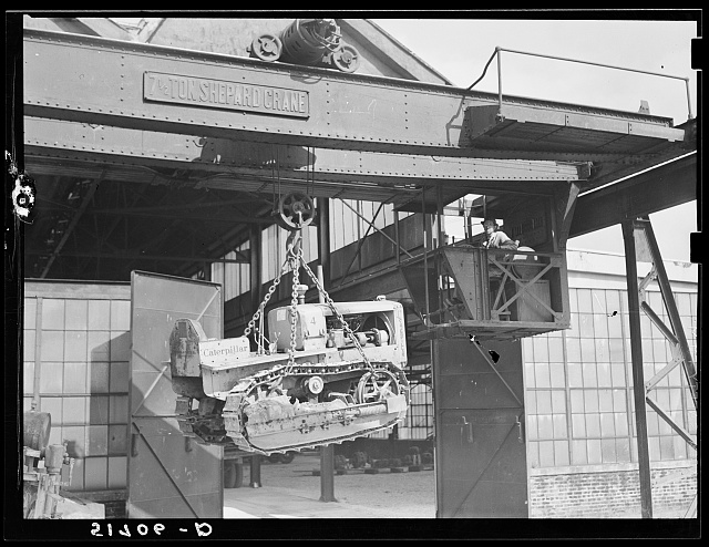 Shepard crane lifting tractor brought to FSA (Farm Security Administration) warehouse depot for repairs. Atlanta, Georgia