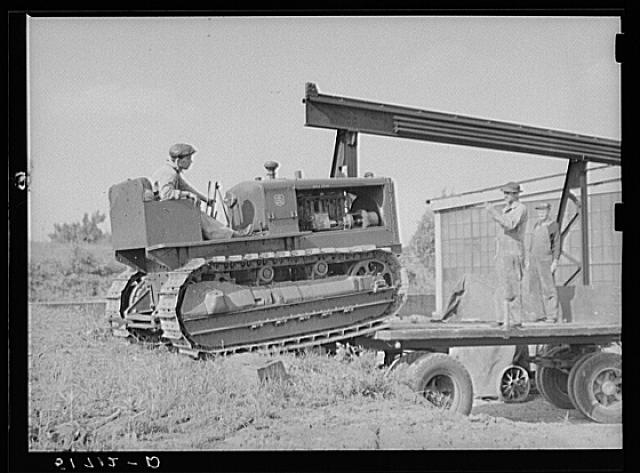 Loading repaired tractor from bank to truck ready to leave FSA (Farm Security Administration) warehouse depot in Atlanta, Georgia