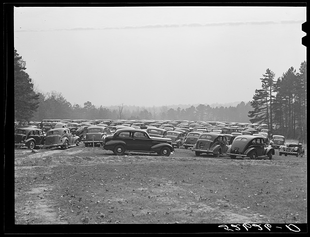 Cars parked in field near Duke University Stadium on day of Duke-Carolina football game. Durham County, North Carolina