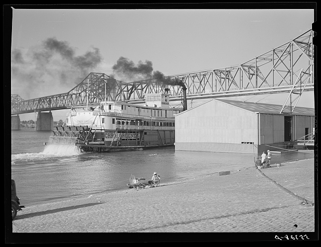 Riverboat carrying cargo leaving dock along waterfront. Louisville, Kentucky. Ohio River
