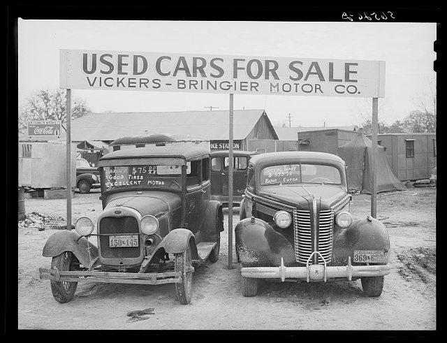 Used cars for sale with signs and prices at service station on main highway near Alexandria, Louisiana
